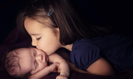 Sister-Kissing-Newborn-Brother-Images-storieo