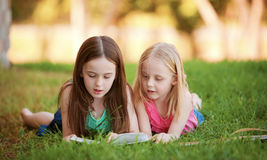 two-young-girls-lying-grass-outdoors-reading-book-siblings-relaxing-together-40162624