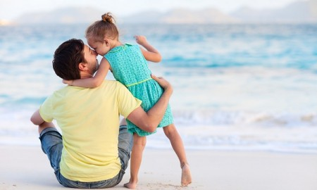 Happy father and his sweet little daughter at beach