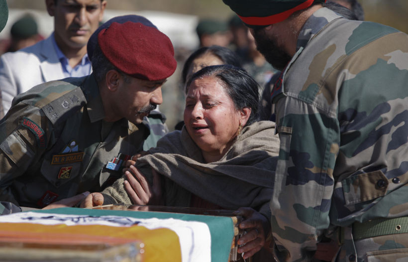 The mother of Indian Army Captain Tushar Mahajan cries next the coffin of his son in Udhampur's military station, Monday, Feb. 22, 2016. Mahajan died from injuries sustained during a gunbattle between Kashmiri rebels and Indian government forces in the Pampore area, Indian-controlled Kashmir. Anti-India sentiment runs deep in India's portion of Kashmir, where rebel groups have been fighting since 1989 for either independence or a merger with neighboring Pakistan. More than 68,000 people have been killed in the armed uprising and ensuing Indian military crackdown. (AP Photo/Channi Anand)