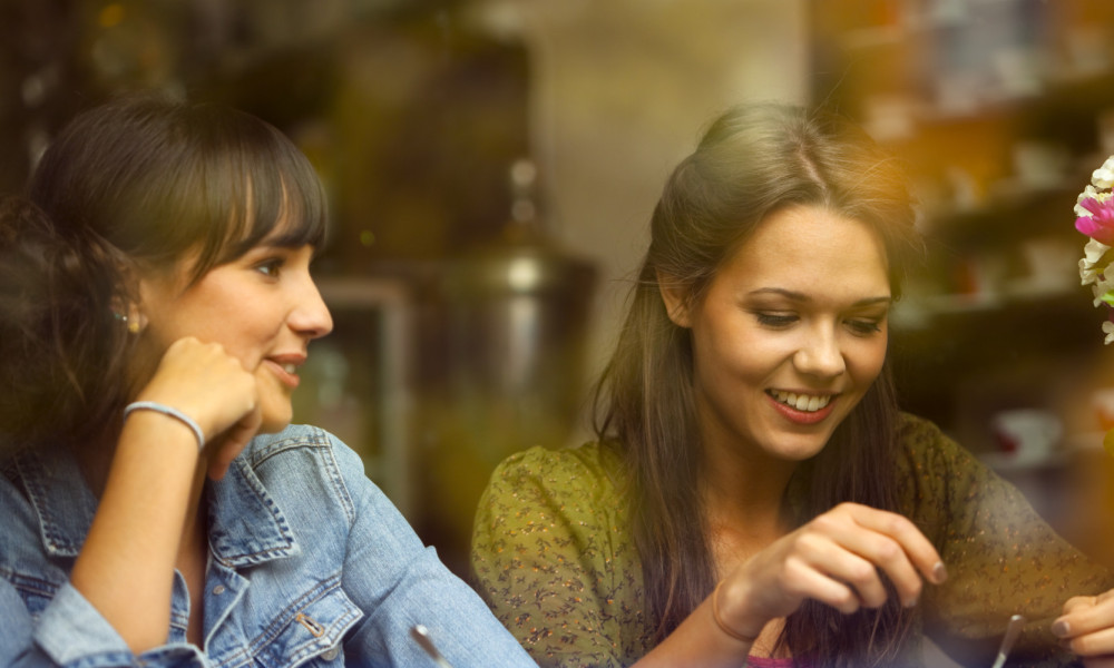 Two Young Beautiful Women Sitting in Cafe, View Through Glass