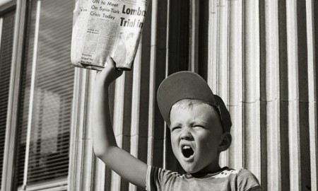 Boy selling newspapers in front of a building
