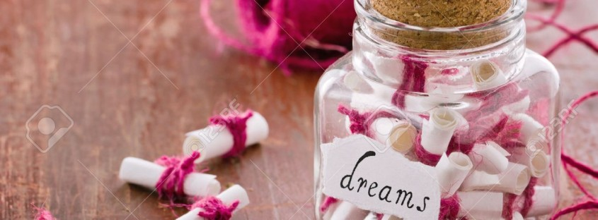 19541463-Dreams-written-on-a-white-rolled-paper-in-a-glass-jar-on-rustic-vintage-wooden-background-dreaming-o-Stock-Photo